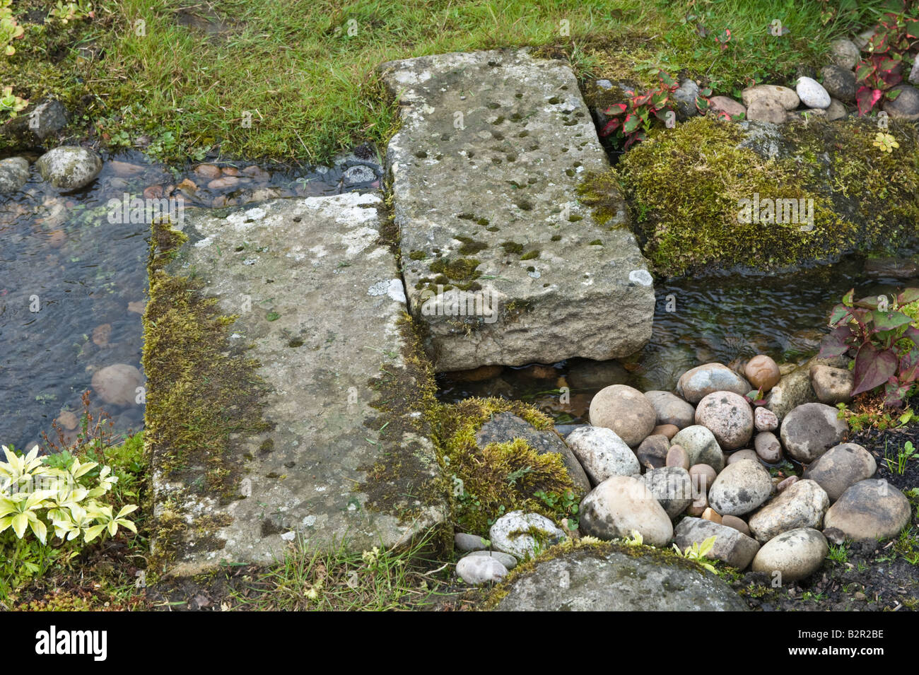 Gridstone stepping stones over stream in garden design by bahaa stock photo royalty free image for Garden design yorkshire