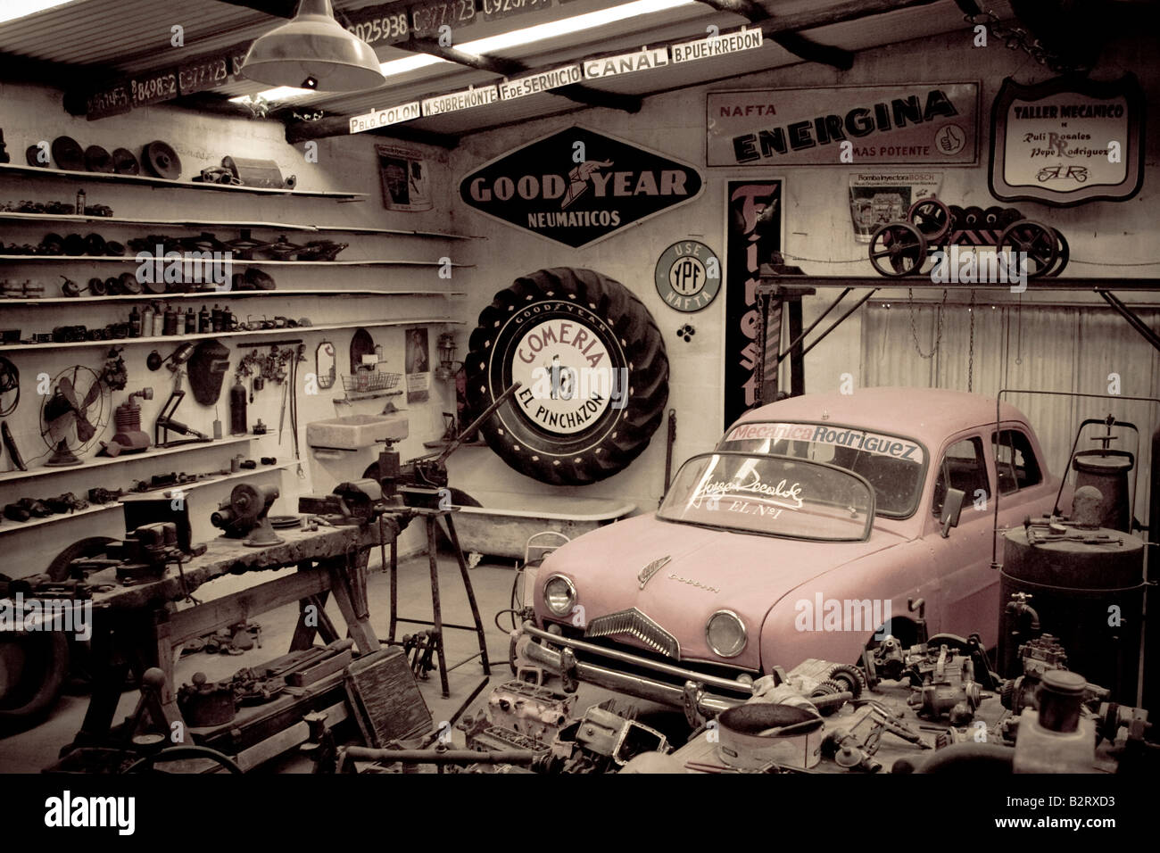 An old car mechanic repair shop in sepia tones exhibited in Rocsen ...