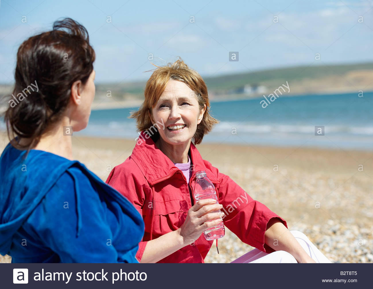 two mature women sitting on beach stock photo, royalty free image