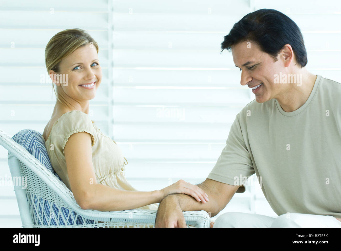 Couple sitting on porch, woman touching mans arm and
