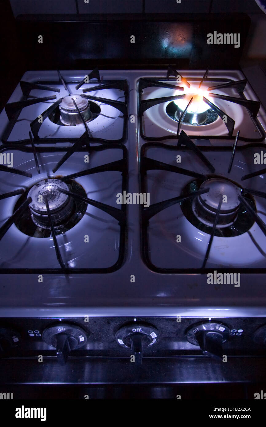 A stove top burner is on, emitting a small blue flame Stock Photo ...