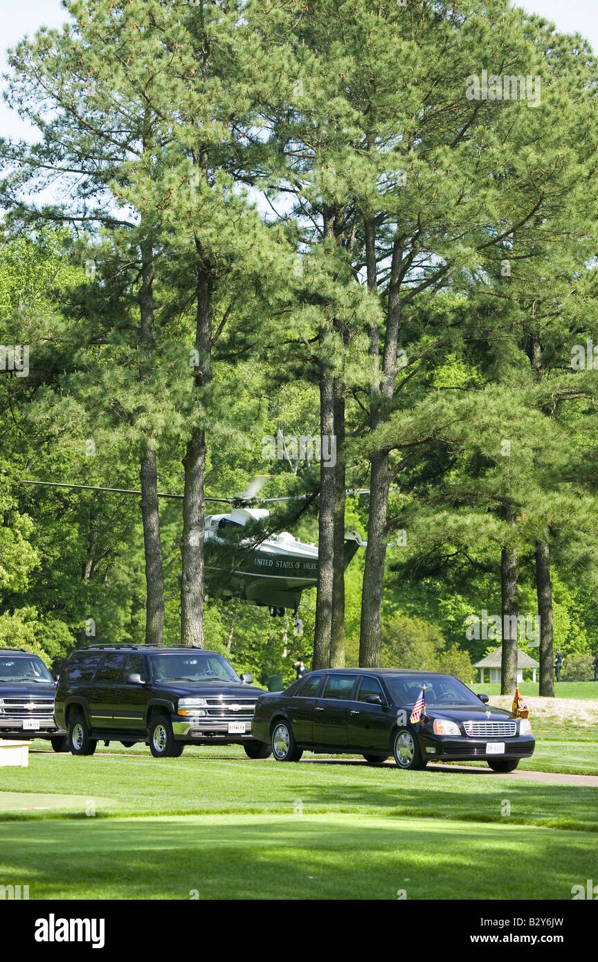 black presidential limo and american flag with motorcade of black suvs and marine one helicopter