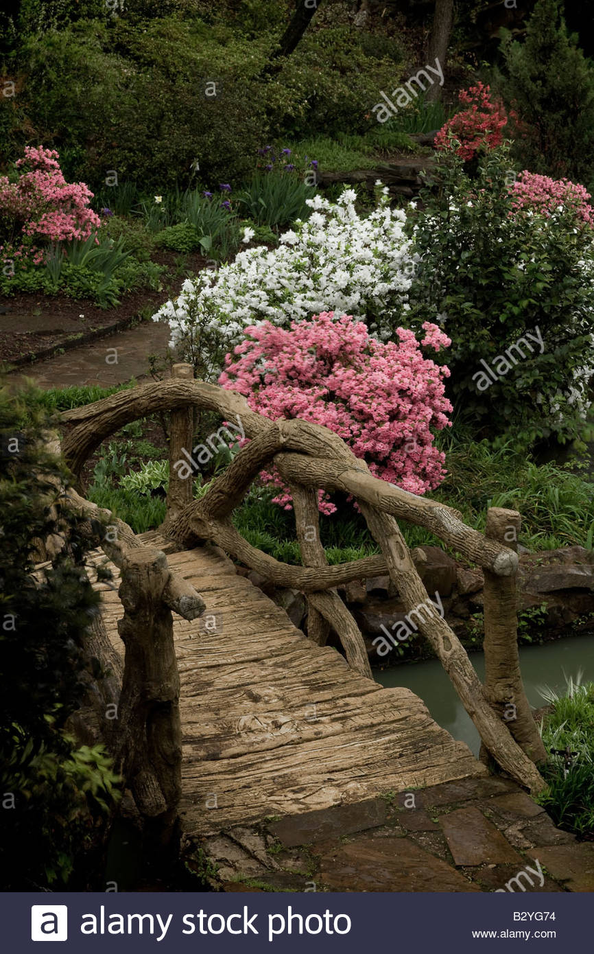 Wooden bridge in a beautiful garden with white and pink flowers blooming