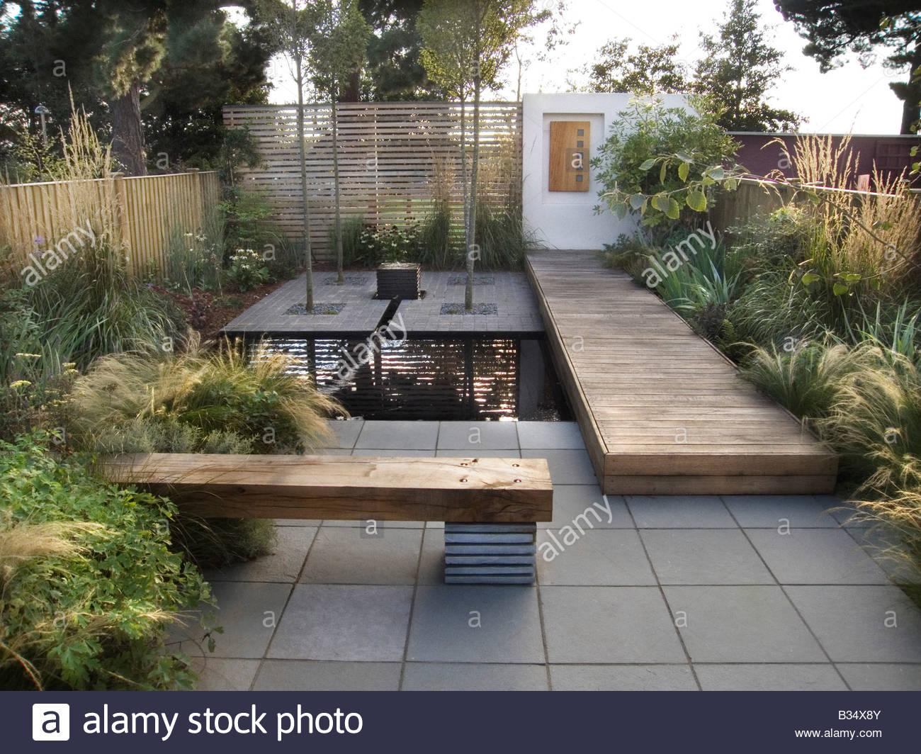 Contemporary urban garden with sleeper bench pond deck for Garden decking with pond