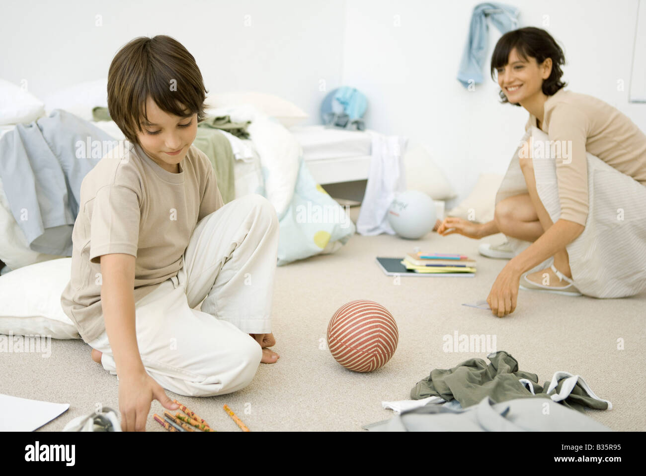 Cleaning Messy Room mother and son crouching down to clean up messy room stock photo