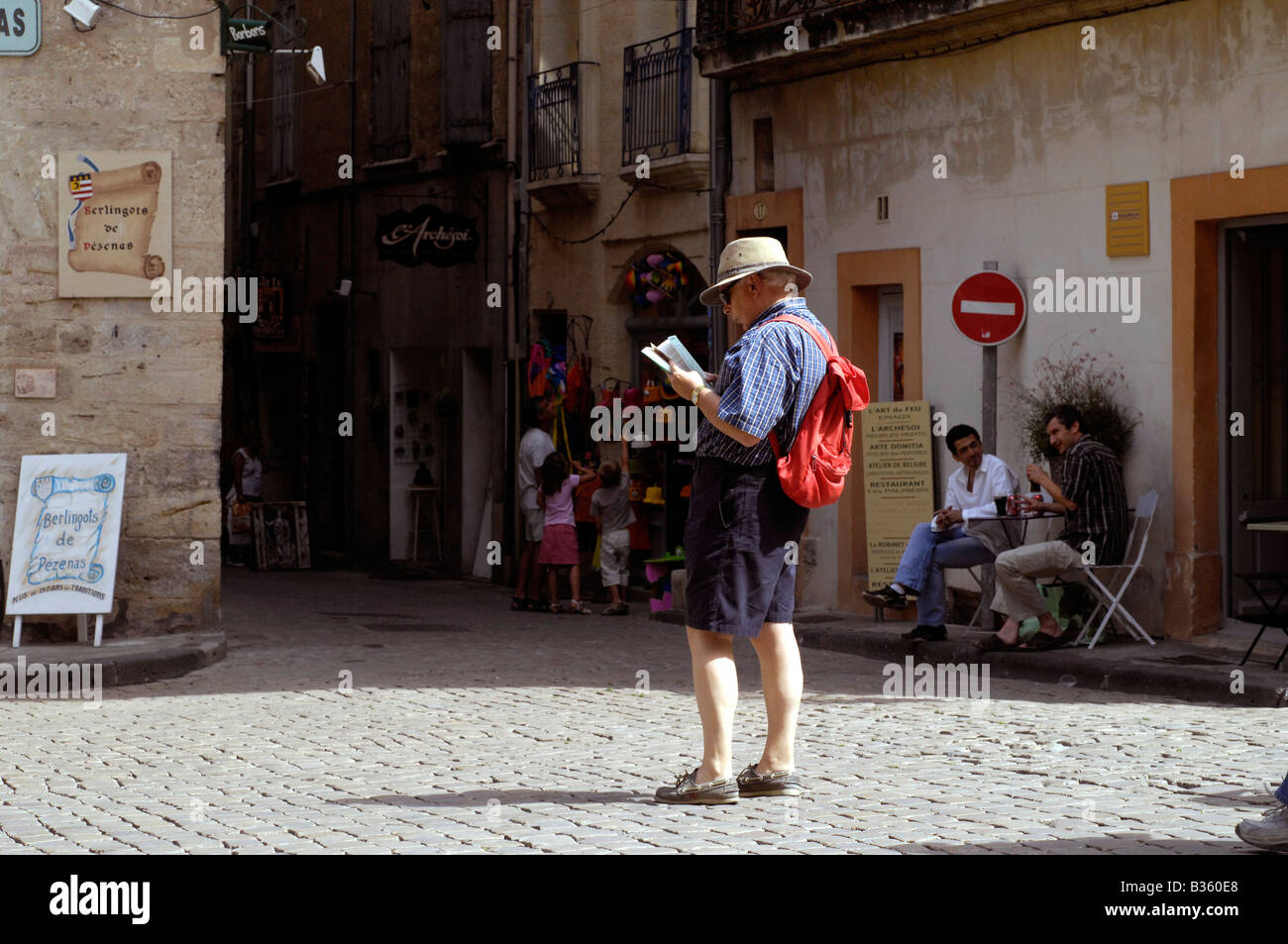 A male visitor studies a tourist map around the historic cobbled