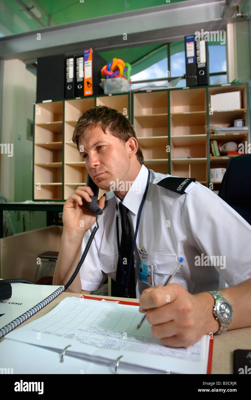 A Security Guard Answers A Phonecall And Makes An Entry In A Log Book Stock Photo Royalty Free