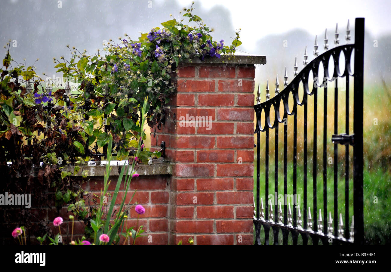 Open wrought iron decorative garden gate hanging off brick pillar stock photo open wrought iron decorative garden gate hanging off brick pillar with clematis covered brick wall ajoining amipublicfo Images