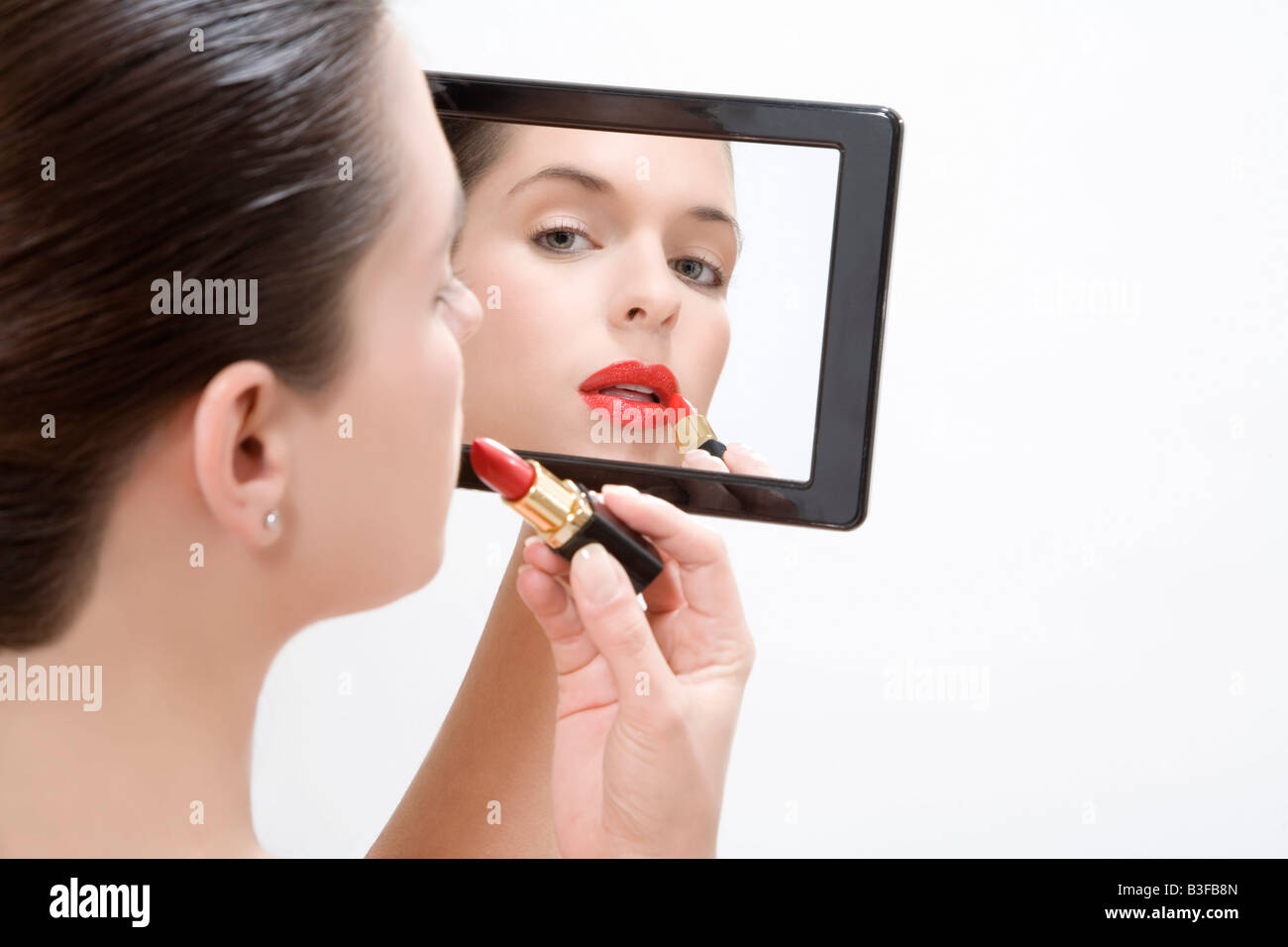 Young woman putting makeup on, portrait Stock Photo, Royalty Free ...