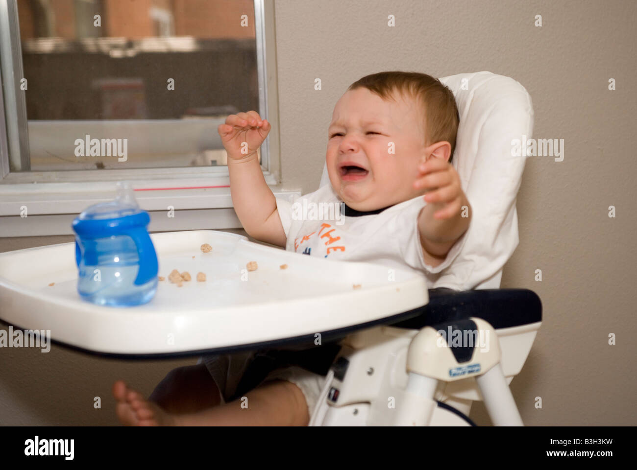 Eight Month Old Baby Boy Crying In His High Chair At Home