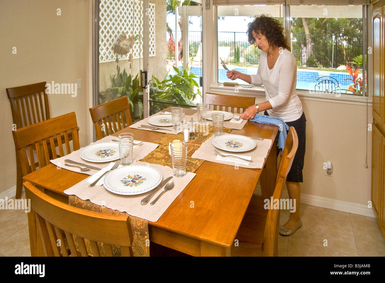 A 50 Year Old Woman Sets Dining Table For Luncheon Guests In Mission Viejo California Note Swimming Pool Outdoor Background