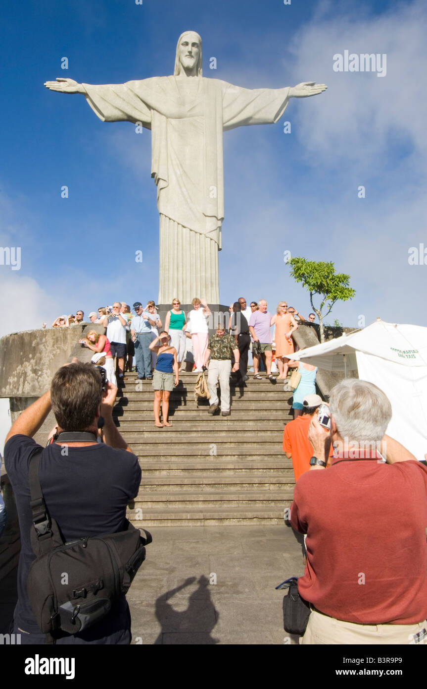A wide angle view of tourists taking photographs of the Christ the Redeemer  (Cristo Redentor) statue overlooking Rio De Janeiro