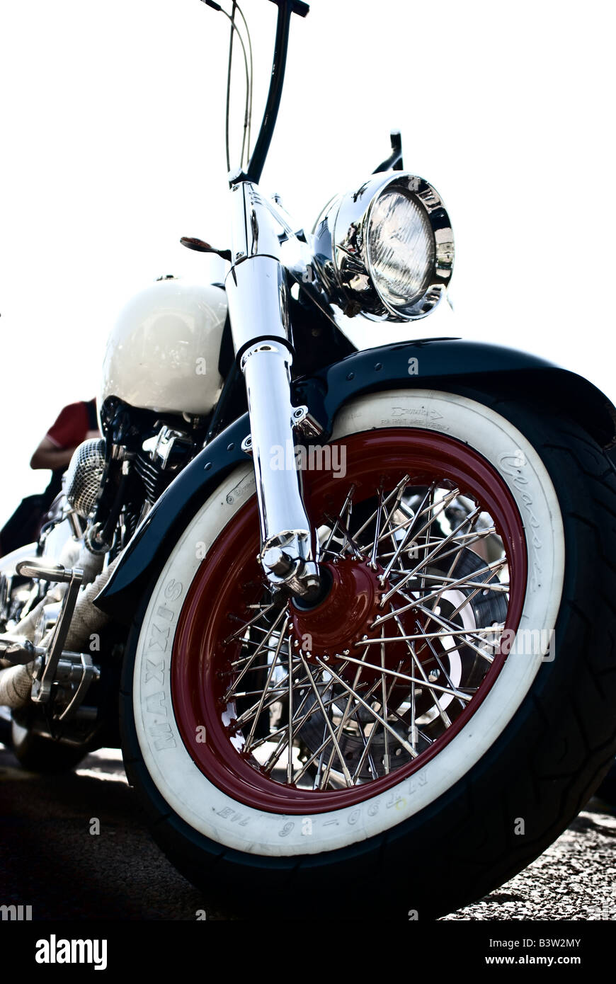 harley davidson motorcycle with white wall tyres on red rims high rise handle bars and
