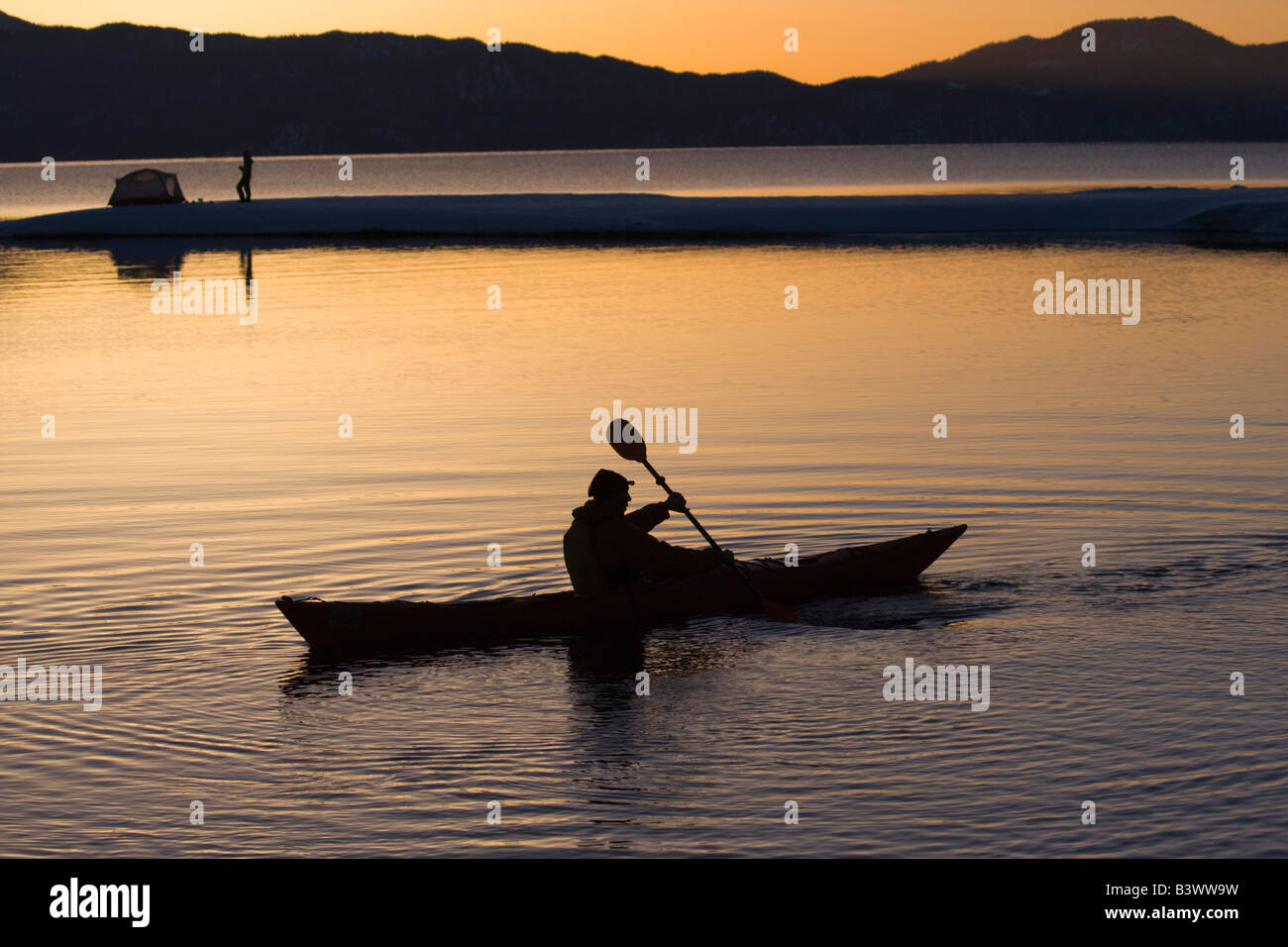Silhouette of a man kayaking in a lake with a woman near a tent in the background Lake Tahoe California USA & Silhouette of a man kayaking in a lake with a woman near a tent in ...