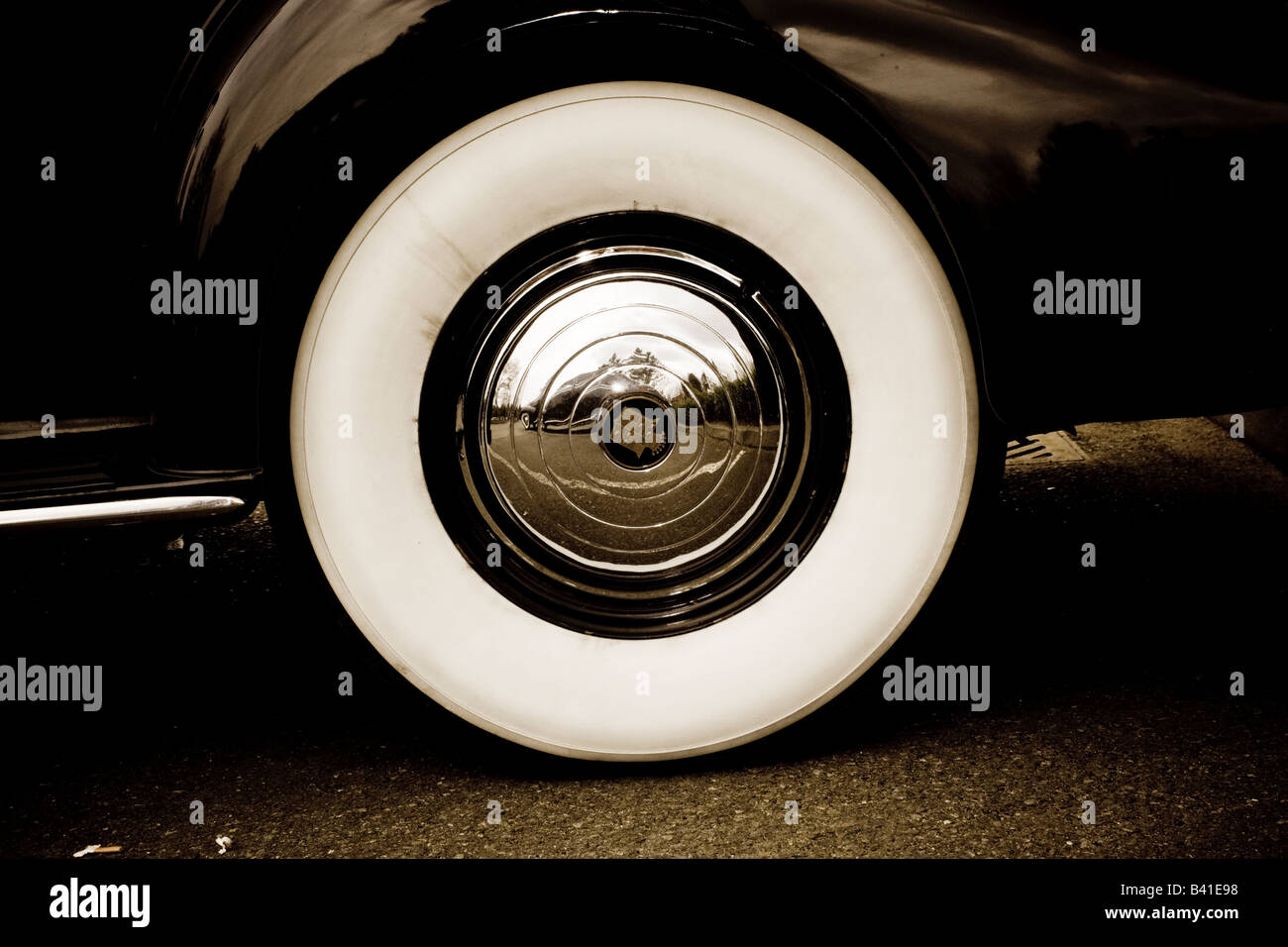 classic cadillac wheel with white wall tyres and polished hub caps stock image