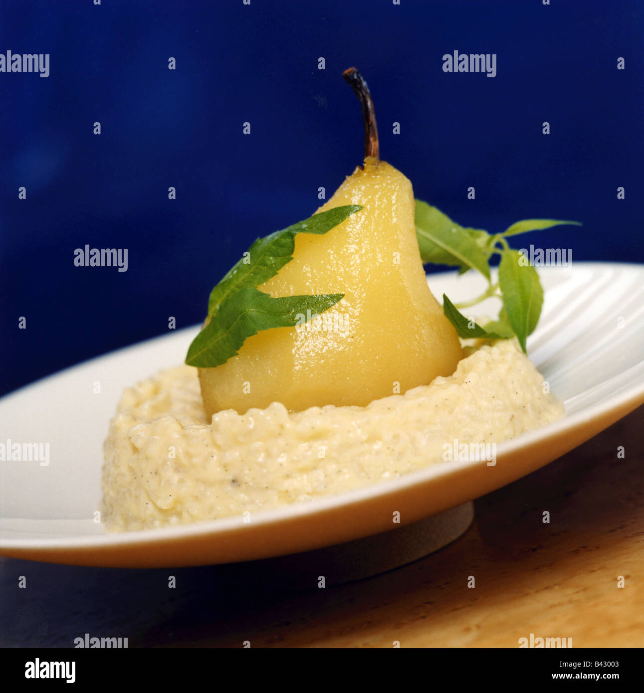 Poached Pear In Verbana On A Bed Of Rice Pudding Stock Photo, Picture ...
