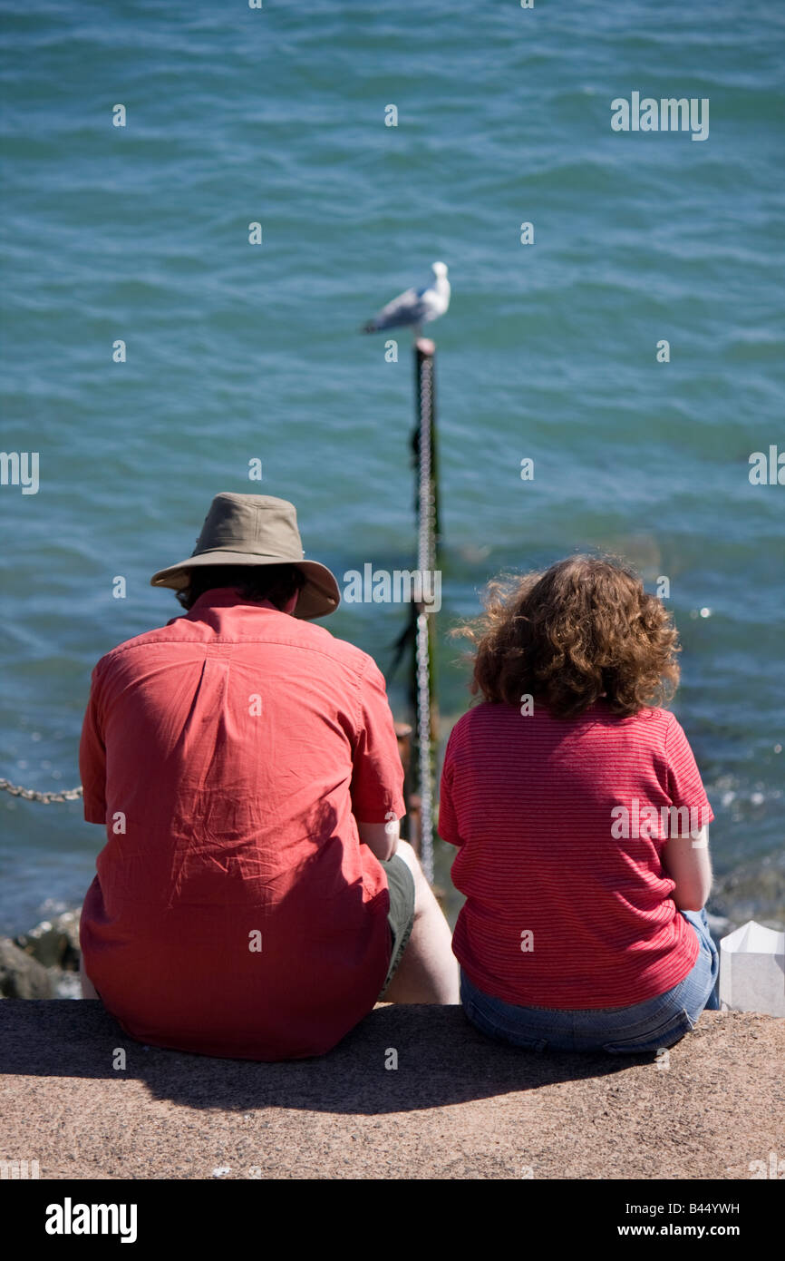 couple-sitting-beside-the-sea-lyme-regis