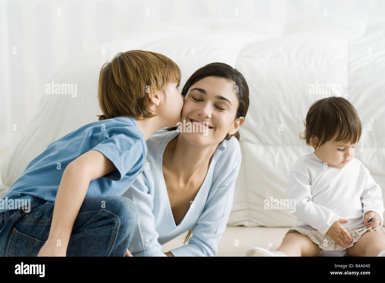 Children girls boy cheek kiss stock photos children girls boy little boy kissing mothers cheek toddler girl sitting nearby stock image thecheapjerseys Images