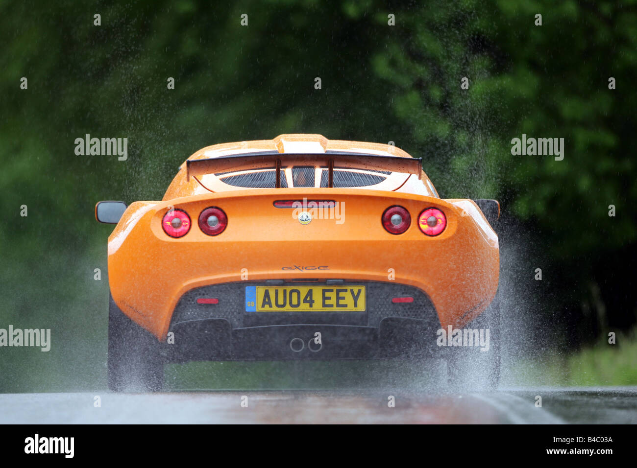 Car lotus exige model year 2004 roadster orange coupecoupe car lotus exige model year 2004 roadster orange coupecoupe driving rear view country road rain wet highway photogr vanachro Images