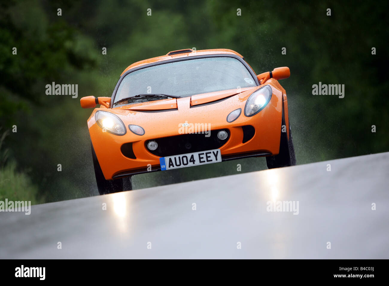 Car lotus exige model year 2004 roadster orange coupecoupe car lotus exige model year 2004 roadster orange coupecoupe driving diagonal from the front frontal view country road vanachro Images
