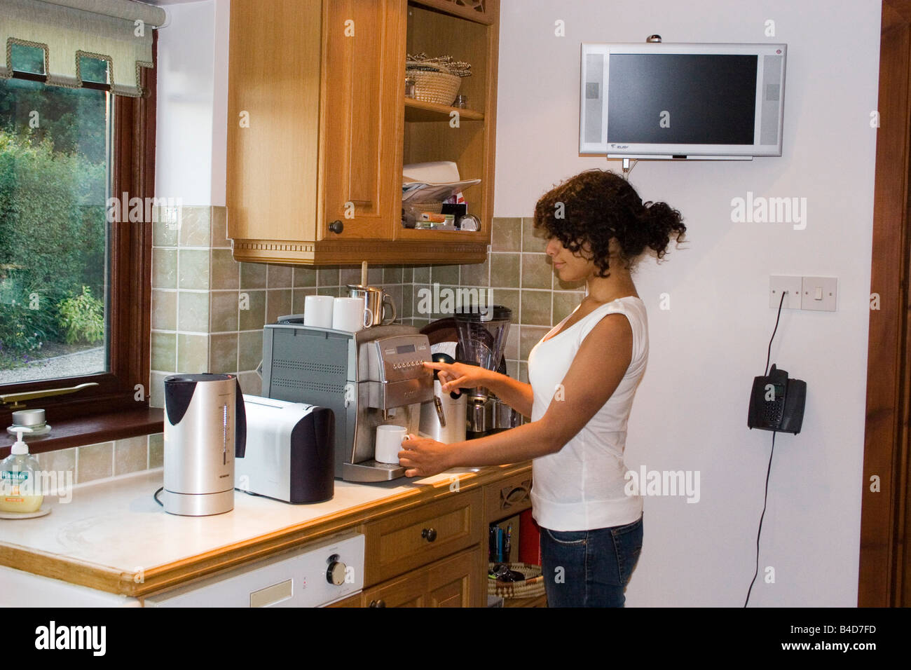 Teenager Or Young Woman Using Array Of Electrical Kitchen Appliances