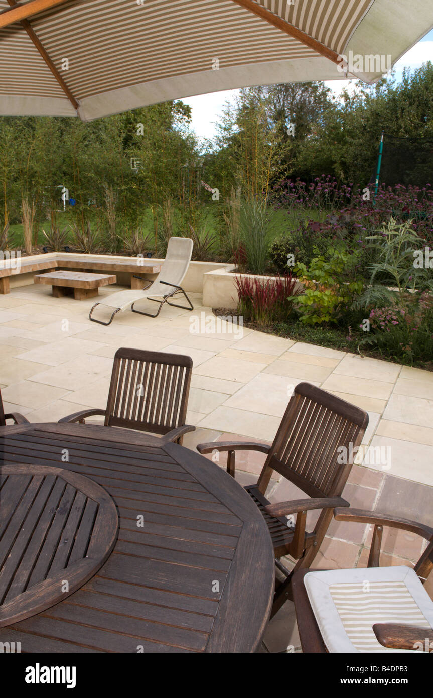 stock photo decking and stone paving in suburban garden table and chairs - Garden Furniture Decking