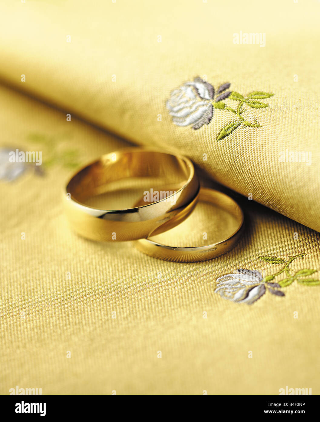 His Hers Gold Wedding Rings On A Fabric Background With Roses