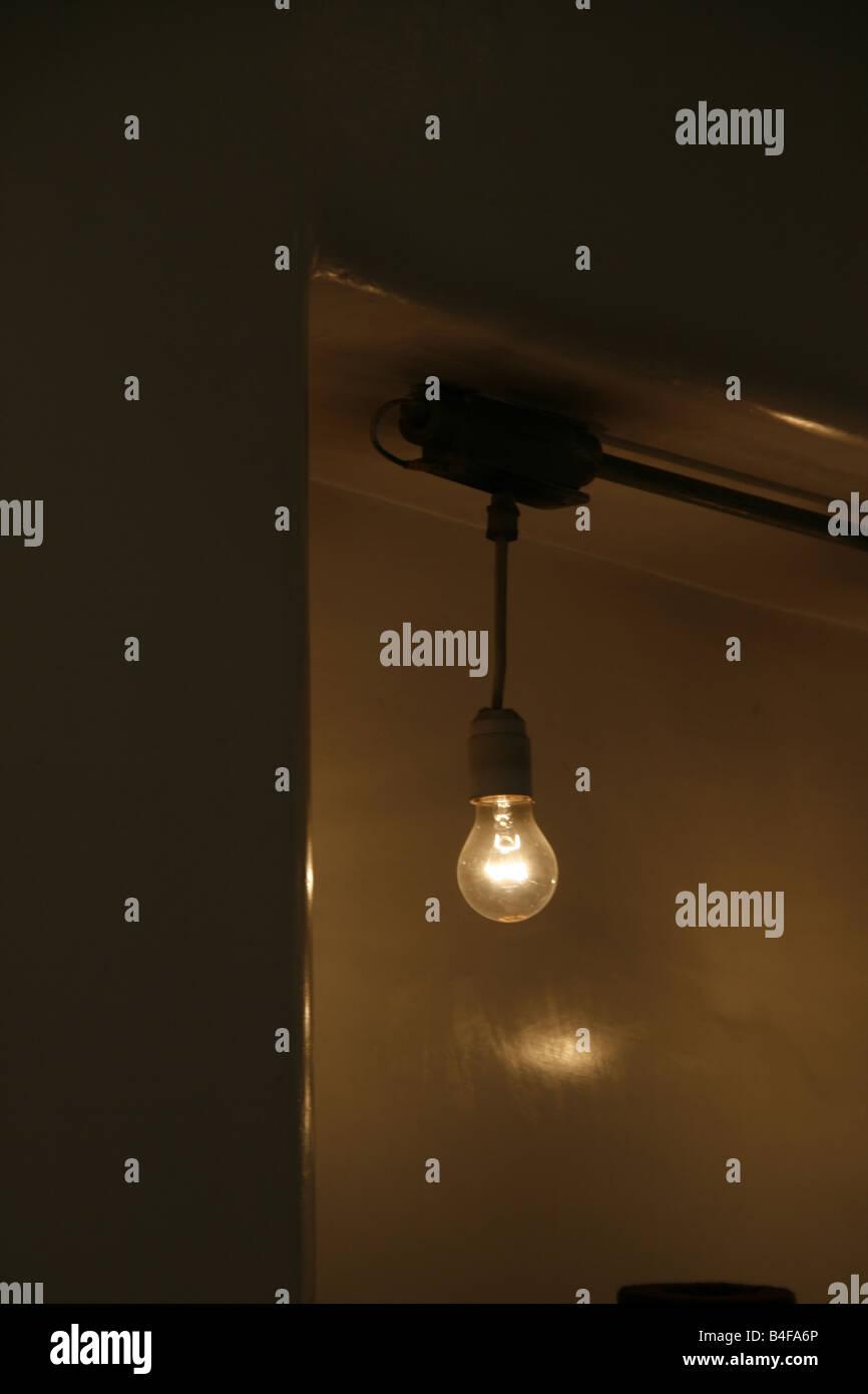 Dark room with light bulb - Stock Photo One Bare Light Bulb In Dark Room At Night