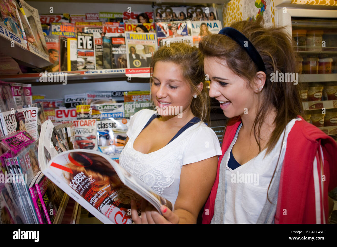2 teenage girls looking at a fashion magazine in a shop. 2 teenage girls looking at a fashion magazine in a shop Stock