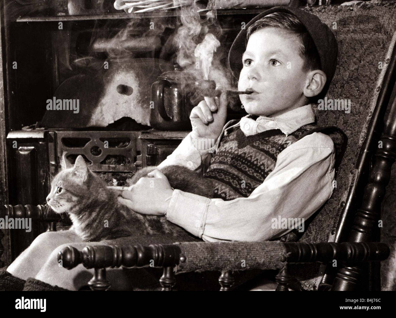 Black child sitting in chair - A Young Boy Smoking A Pipe And Stroking A Cat Sitting In A Chair Looking Into