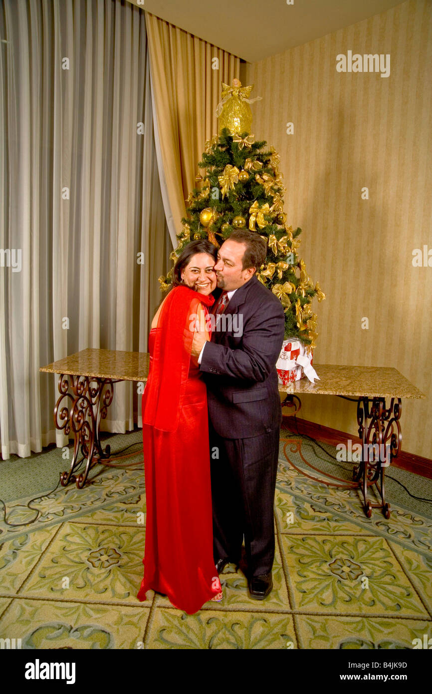 a couple pose for a formal picture in front of a christmas tree at