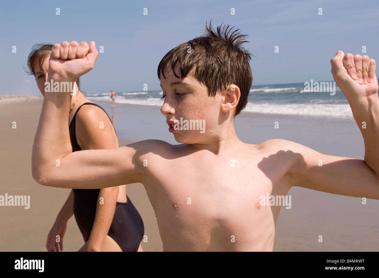 A Boy Flexes His Muscles On The Beach As A Woman Walks By And Looks