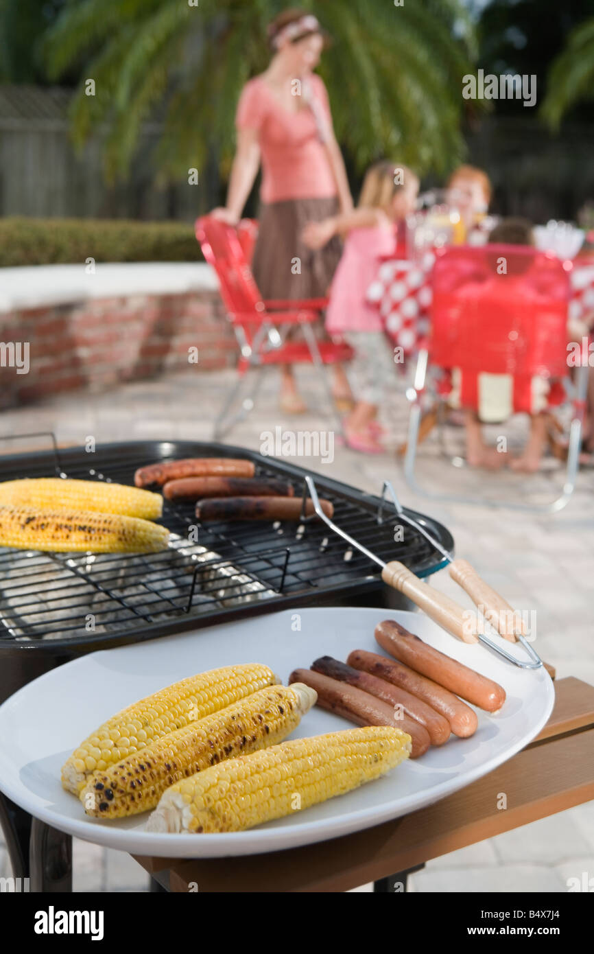 grilled hotdogs and corn on backyard grill stock photo royalty
