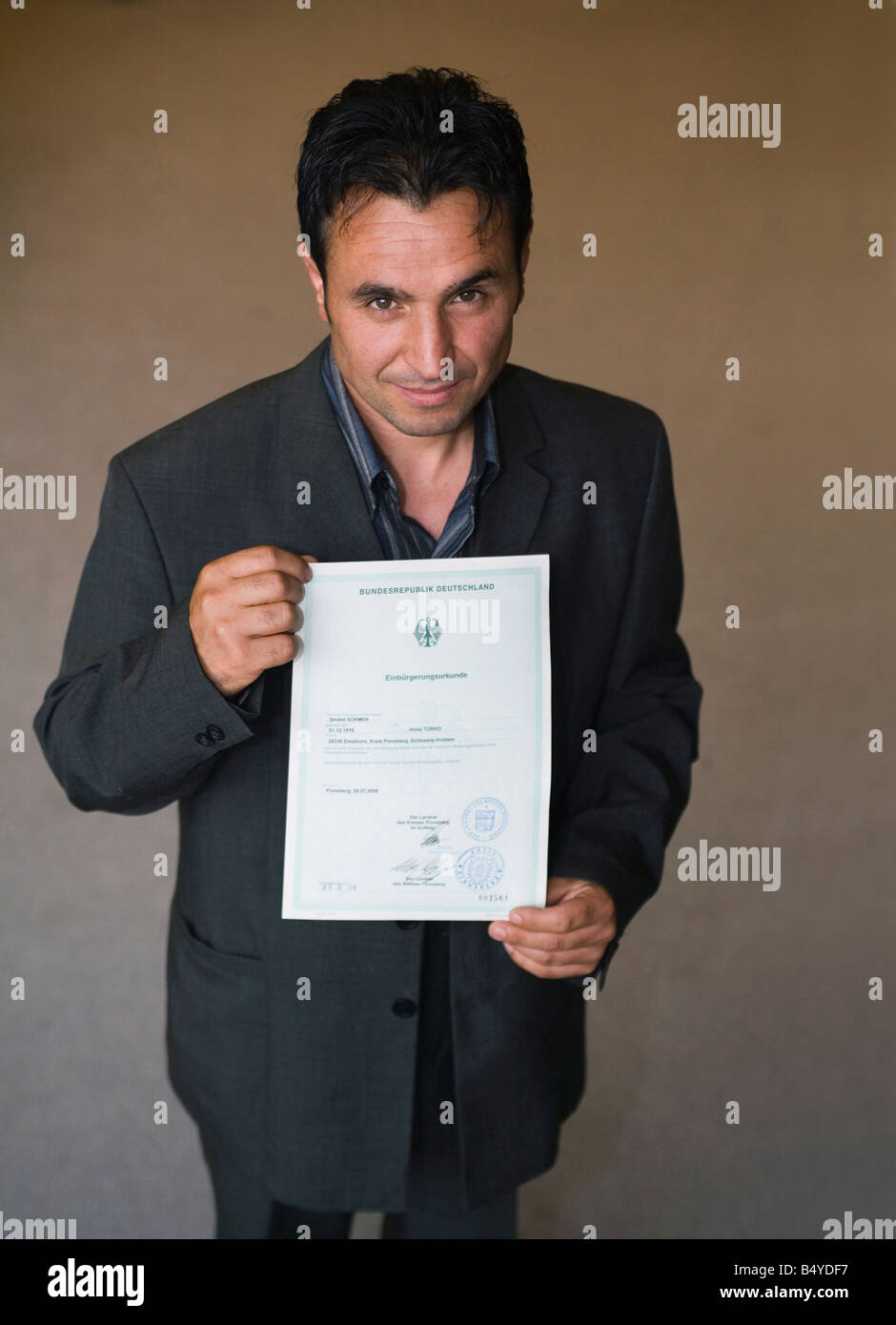 After the naturalization ceremony with the conferment of the after the naturalization ceremony with the conferment of the german citizenship immigrant with naturalization certificate 1betcityfo Choice Image