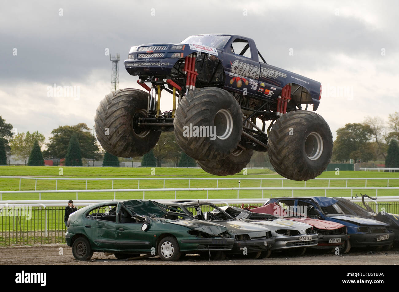 Monster Truck Jumping Over Crushed Cars In A Race Stock Photo