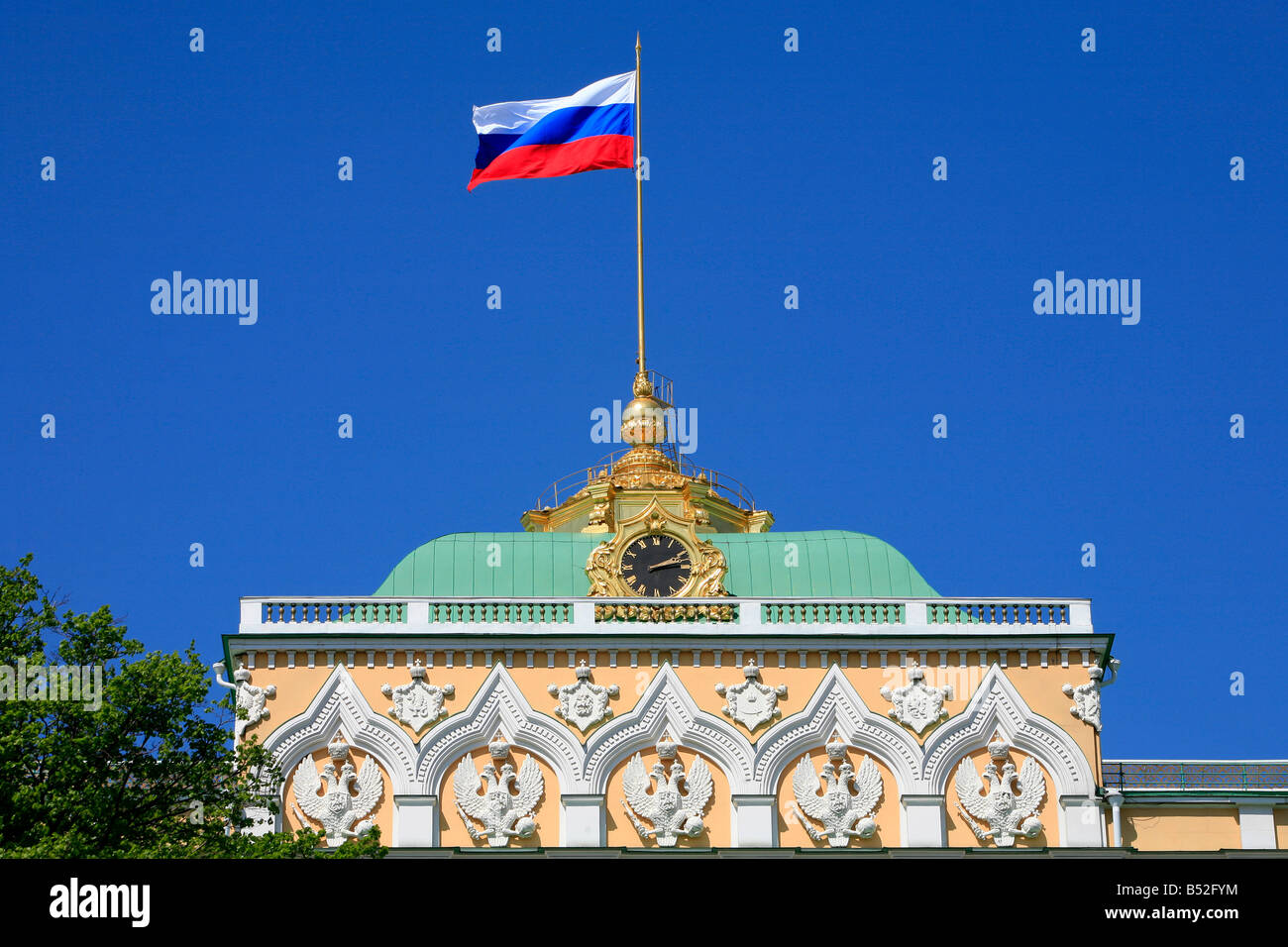 the russian flag flying over the grand kremlin palace in moscow