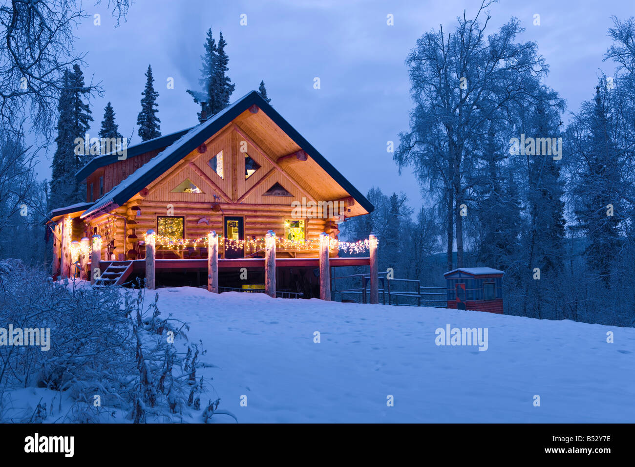 Log cabin in the woods decorated with christmas lights at for Alaska cottage