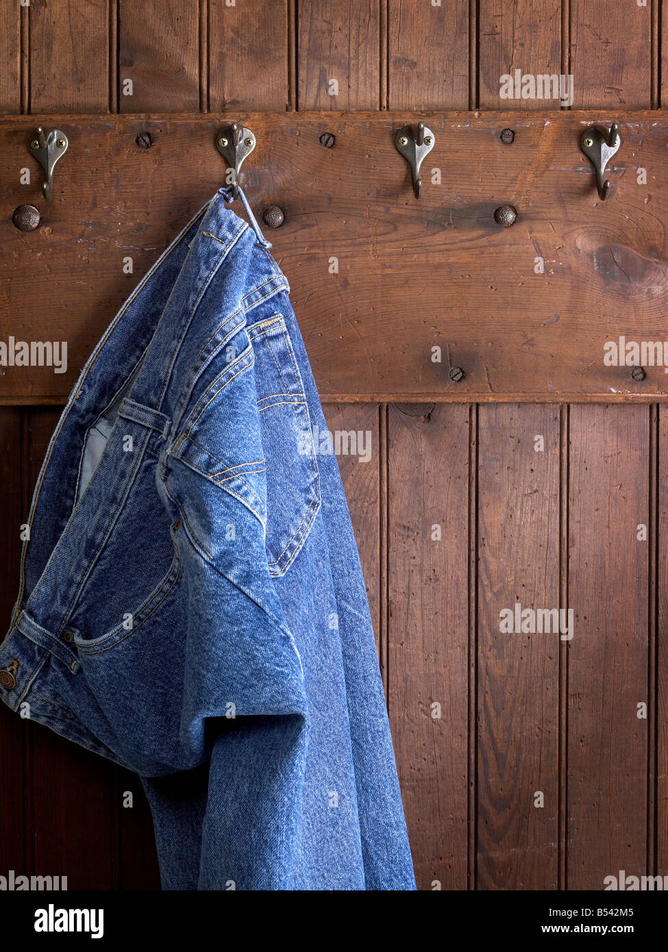 Blue Jeans Hanging On Hook Weathered Wood Wall Stock Photo