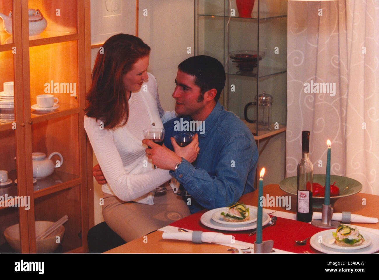 A couple enjoy a romantic candlelit dinner at home Stock Photo ...