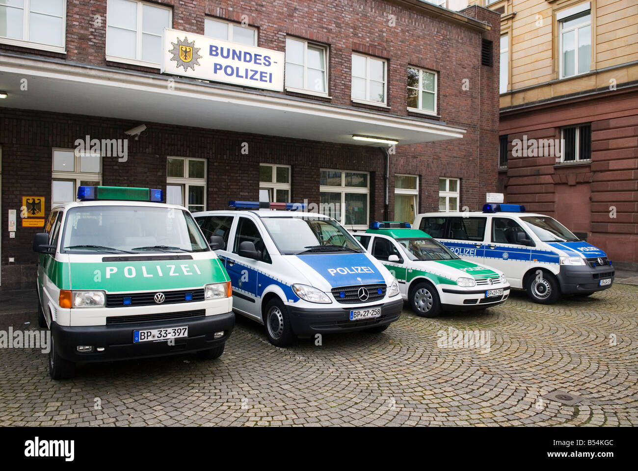 old style green and new style blue police cars are lined up in ...