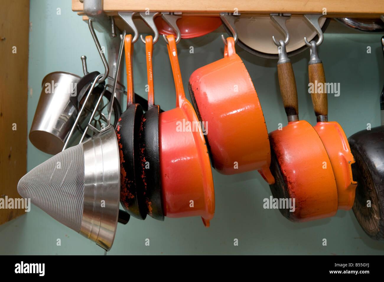 Le creuset cast iron saucepan set - Stock Photo Set Of Orange Cast Iron Le Creuset Pans Pots Saucepan Saucepans Utensils Hanging From Hooks In A Kitchen Uk