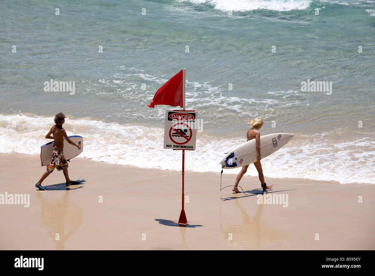 people carrying surf boards past danger no swimming sign