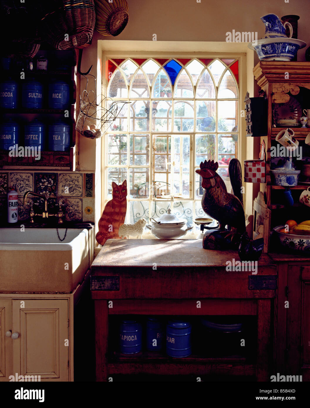 Glass cat ornaments - Gothic Style Window With Stained Glass Inserts Above Ceramic Sink And Worktop With Cat And Chicken Ornaments In Cottage Kitchen