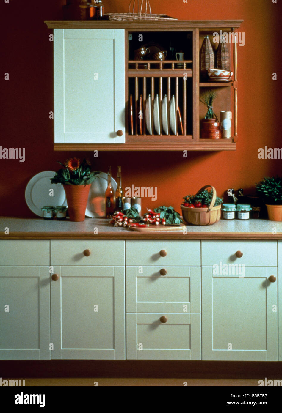 plate rack and wooden shelves on wall unit in red kitchen with