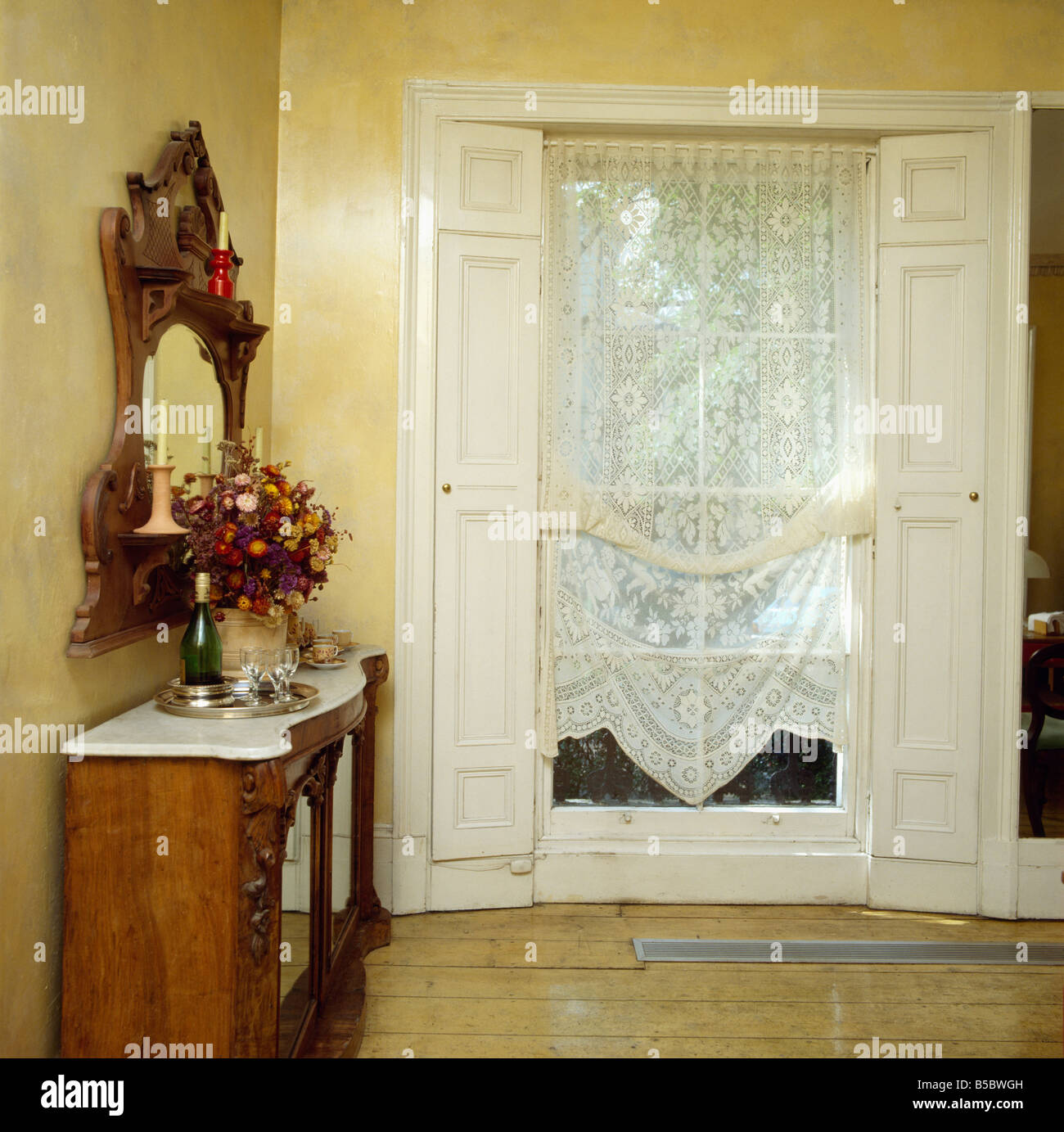 Window With White Lace Drapes And Shutters In Dining Room Ornate Mahogany Mirror Above