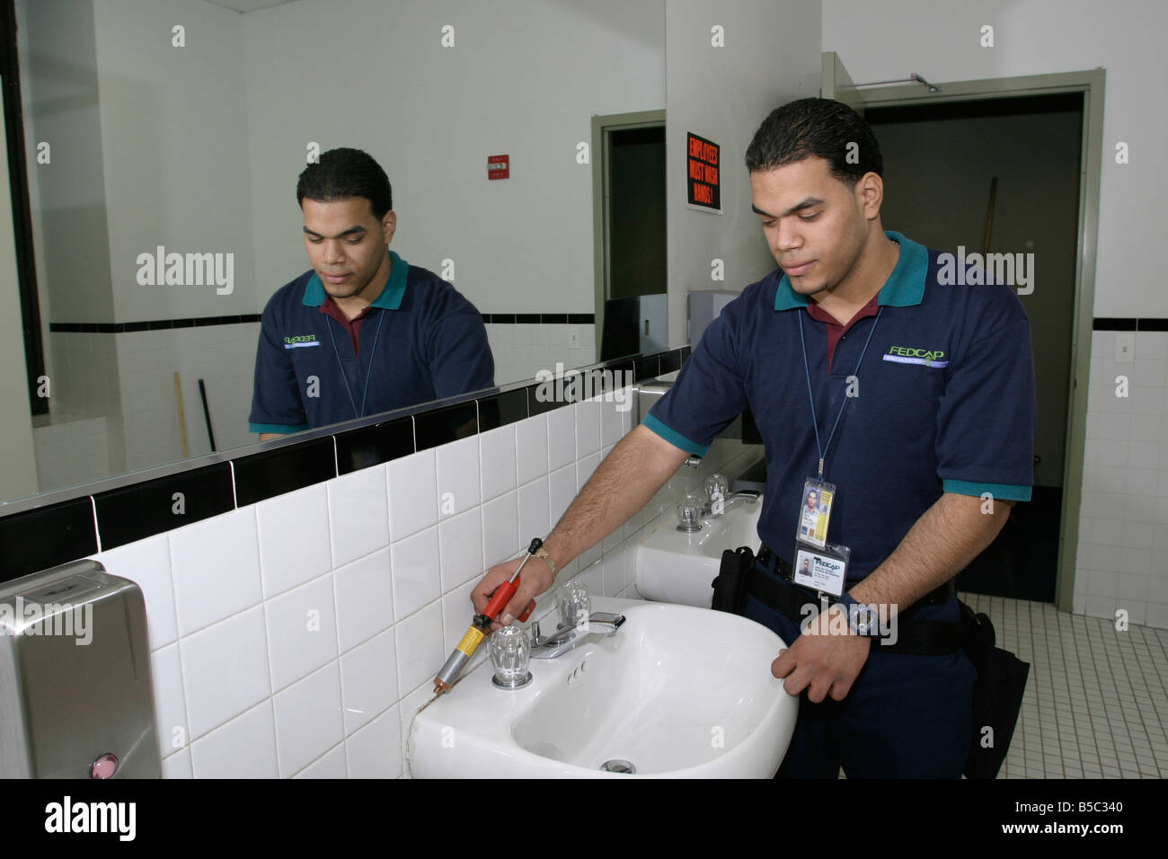 custodial worker does exterminator chores in a bathroom stock custodial worker does exterminator chores in a bathroom