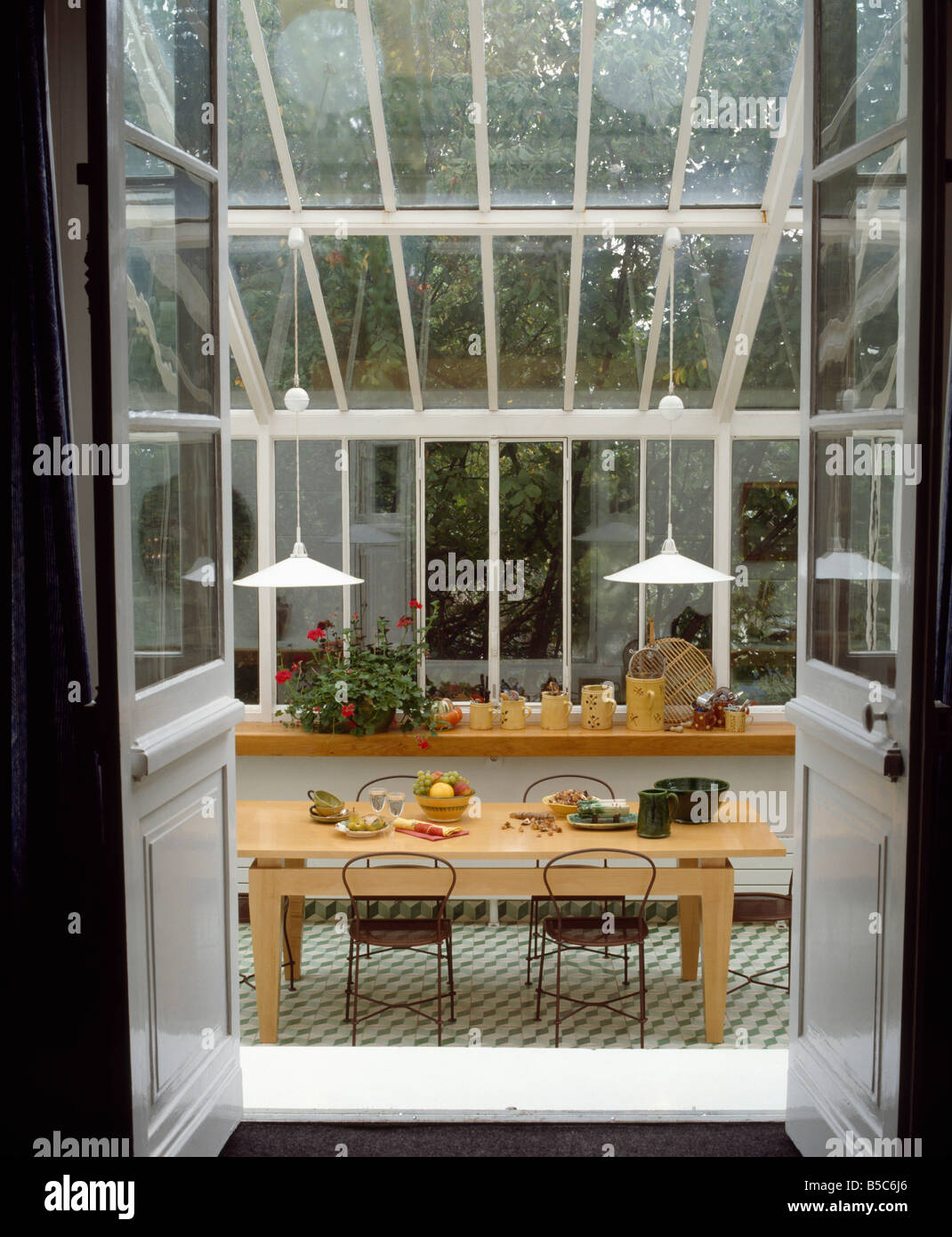 Half Glazed Double Doors Open To Modern Conservatory Dining Room With Pendant Lights Above Pale Wooden Table