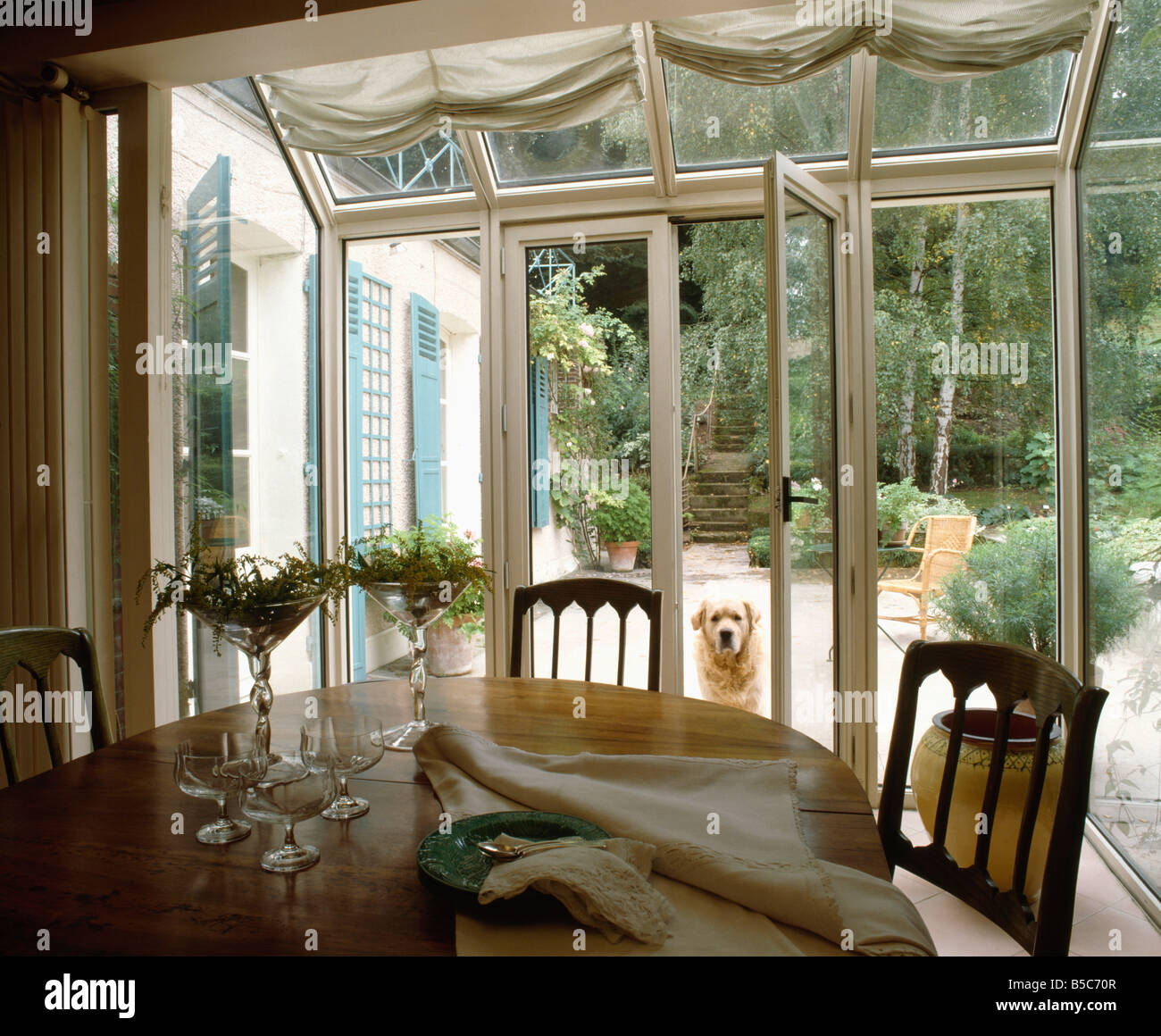 Chairs and circular table in conservatory dining room with French ...