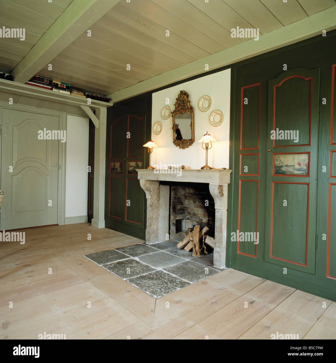 Slate tiles set into wooden floor in front of fireplace with stone slate tiles set into wooden floor in front of fireplace with stone mantelpiece in german country hall with green paneling dailygadgetfo Image collections