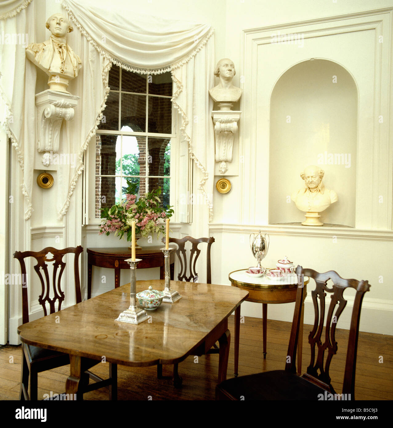 classical busts on corbels on either of window with cream drapes classical busts on corbels on either of window with cream drapes in cream dining room with alcove and antique furniture